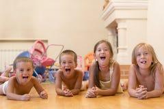 Gruppen av fyra barn som ligger på golvet Lögn för fyra lycklig barn på golvet arkivbild