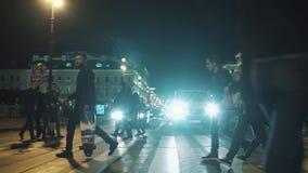 Gruppen av gångare går över övergångsställe för nattstadsväg lager videofilmer
