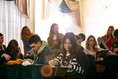 Gruppen av gladlynta lyckliga studenter som sitter i en hörsal för kurs arkivbild