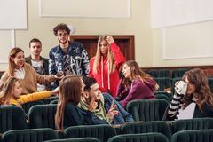 Gruppen av gladlynta lyckliga studenter som sitter i en hörsal för kurs royaltyfria foton
