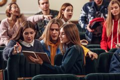 Gruppen av gladlynta lyckliga studenter som sitter i en hörsal för kurs royaltyfri bild