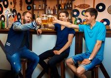 Gruppen av grabbar som dricker öl i en stång och, har någon gyckel Arkivfoto