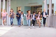 Gruppen av grundskolan lurar spring i en skolakorridor arkivbild