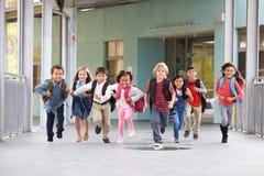Gruppen av grundskolan lurar spring i en skolakorridor royaltyfria foton