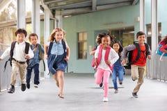 Gruppen av grundskolan lurar spring i en skolakorridor royaltyfri fotografi
