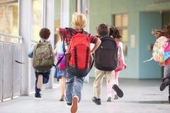 Gruppen av grundskolan lurar spring på skolan, baksidasikt royaltyfri fotografi