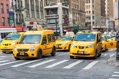 Gruppen av gula taxitaxiar rusar affärsmannen och turister runt om Manhattan Royaltyfri Bild