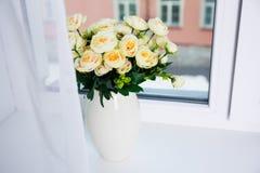 Gruppen av härligt steg blommor i keramisk vas på ett fönster Royaltyfri Foto