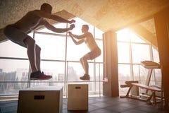 Gruppen av idrotts- folkjumpin över något boxas i enutbildning idrottshall Arkivfoton