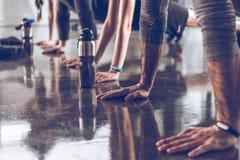 Gruppen av idrotts- ungdomar, i att göra för sportswear, skjuter ups eller plankan på idrottshallen royaltyfri bild
