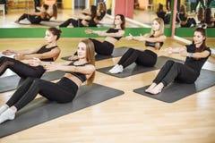 Gruppen av idrotts- utföra för unga kvinnor sitter upp övningar för att förstärka deras buk- muskler för kärnan på konditionutbil arkivbilder