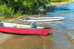 Gruppen av kanoter och kajaker på en sjökust parkerar in arkivfoto