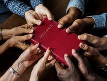 Gruppen av kristet folk är den hållande heliga bibeln arkivfoton