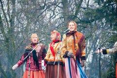 Gruppen av kvinnor i traditionella ryska clothers sjunger en sång på Maslenitsa i Moskva Royaltyfri Bild