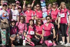 Gruppen av kvinnor med rosa skjortor poserar för ett gruppfoto Royaltyfri Foto