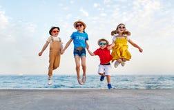 Gruppen av lyckliga barn hoppar vid havet i sommar royaltyfri fotografi
