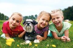 Gruppen av lyckliga barn som spelar på grönt gräs i vår, parkerar Royaltyfri Foto