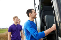 Gruppen av lyckliga manliga passagerare som stiger ombord lopp, bussar royaltyfri fotografi
