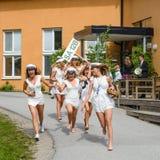 Gruppen av lyckliga tonåringar som bär avläggande av examen, caps spring ut från skola efter avläggande av examen från högstadiet Arkivbild