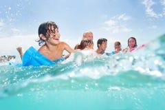 Gruppen av lyckliga ungar spelar i havet på matrass Arkivfoto