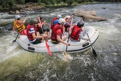 Gruppen av män och kvinnor, tycker om rafting på floden royaltyfri bild