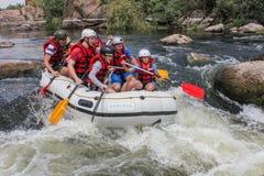 Gruppen av män och kvinnor, tycker om vatten som rafting på floden arkivfoton