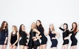Gruppen av många kyler moderna flickavänner i den olika klänningen för modestilsvart som har tillsammans gyckel som isoleras på w Arkivfoton