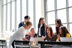 Gruppen av mångfaldfolk Team att le och upphetsat i framgångarbete med bärbara datorn på det moderna kontoret royaltyfri foto