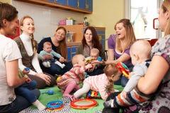 Gruppen av mödrar med behandla som ett barn på Playgroup royaltyfria foton