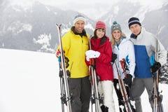 Gruppen av medelåldriga par skidar på ferie Arkivbild