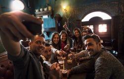 Gruppen av millennial folk tar en selfie i en bar som dricker öl royaltyfri fotografi