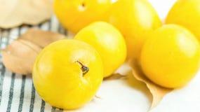 Gruppen av mogna saftiga organiska gula plommoner torkar orange höstsidor på den vita bomullshandduken Autumn Fall Produce royaltyfri fotografi