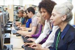 Gruppen av mogna studenter som arbetar på datorer med, handleder fotografering för bildbyråer