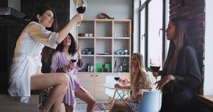 Gruppen av mycket attraktiva vändamer tycker om deras ungmöparti hemma i en modern studiodesign dem som dricker stock video