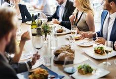 Gruppen av olikt folk har lunch tillsammans arkivfoton