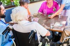 Gruppen av pensionärer och sjuksköterskan som spelar kort vilar in, hemmet Royaltyfri Fotografi