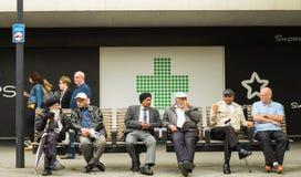 Gruppen av pensionärer som sitter på, parkerar bänken som talar och ler arkivfoton