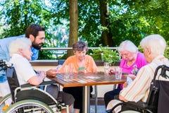 Gruppen av pensionärer och sjuksköterskan som spelar kort vilar in, hemmet Arkivbilder