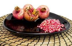 Gruppen av pomegranades bär frukt och nytt frö på en svart maträtt och en träplatta för mat och sunda begrepp Royaltyfri Bild