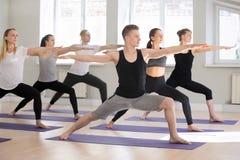 Gruppen av praktiserande yoga för sportigt folk som gör krigare två, poserar arkivbild