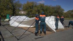 Gruppen av räddare som ställer in - upp ett arméfälttält, utplacerar tältplatsen på blåsig dag lager videofilmer