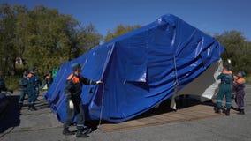 Gruppen av räddare som ställer in - upp ett arméfälttält, utplacerar tältplatsen på blåsig dag arkivfilmer