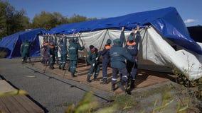 Gruppen av räddare som ställer in - upp ett arméfälttält, utplacerar tältplatsen på blåsig dag stock video