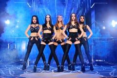 Gruppen av sexigt gå-går dansare som bär svarta dräkter Royaltyfri Bild