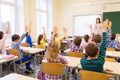 Gruppen av skolan lurar att lyfta händer i klassrum Fotografering för Bildbyråer