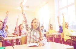 Gruppen av skolan lurar att lyfta händer i klassrum Royaltyfria Bilder