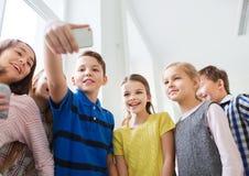 Gruppen av skolan lurar att ta selfie med smartphonen Arkivfoton