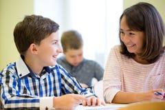 Gruppen av skolan lurar handstilprovet i klassrum Arkivbild