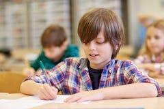 Gruppen av skolan lurar handstilprovet i klassrum Arkivbilder