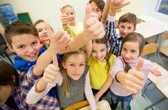 Gruppen av skolan lurar upp visningtummar Royaltyfri Fotografi